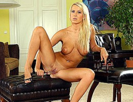 Busty blonde teen babe fondles herself on a black couch