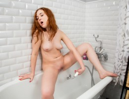 Spicy redhead Arial enjoys spending time in the bathroom if it means she gets to satisfy her lusty hairy pussy. Climbing into the tub, she uses the wand to spray down her puffy nipple titties and then pulls aside her panties to aim the spray nice and low