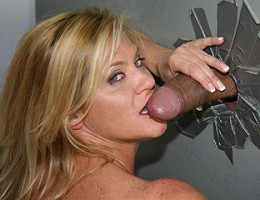 Ginger Lynn gulps a giant black cock in a gloryhole