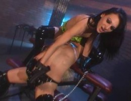 Two hot latex dressed babes licking and dildo fucking